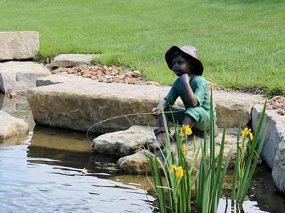 Beautifully landscaped pond with a bronze statue and fountain in the yard of a Bridge Home residence